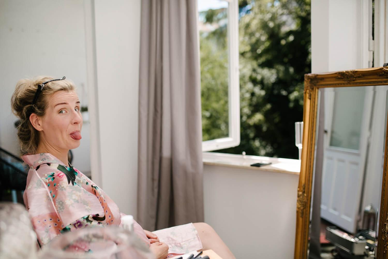 Braut streckt dem Fotografen die Zunge raus und sitzt beim Getting Ready vor einem Spiegel.