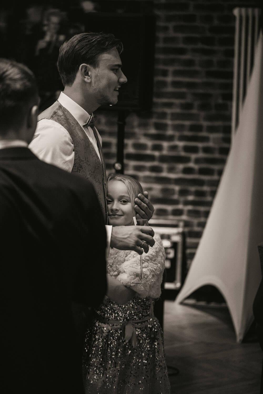 Braeutigam haelt seine Nichte im Arm und streichelt ihren Kopf