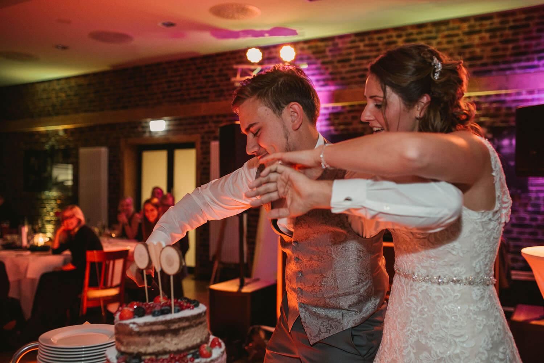 Brautpaar schneidet den Kuchen an und der Braeutigam versucht die Braut abzuwehren. Hochzeitsfotos in Belm.
