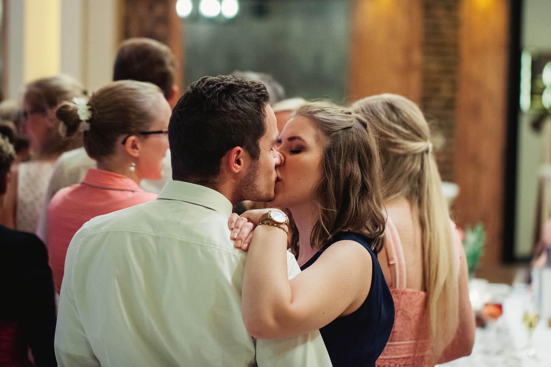 Gaeste kuessen sich, während sie für die Hochzeitstorte anstehen. Hochzeitsfotos in Belm.