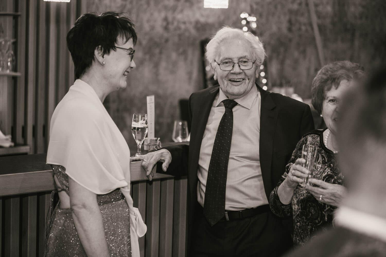Mutter und Großeltern des Braeutigams stehen lachend an der Bar bei Lecon. Hochzeitsfotos in Belm.