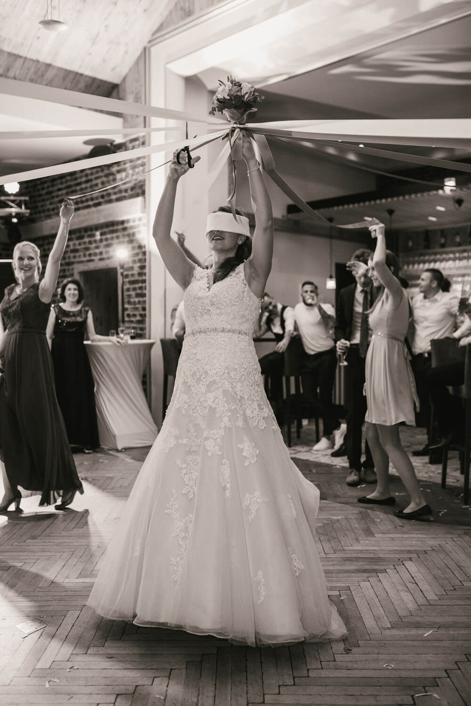 Braut schneidet mit verbundenen Augen Baender vom Brautstrauß durch