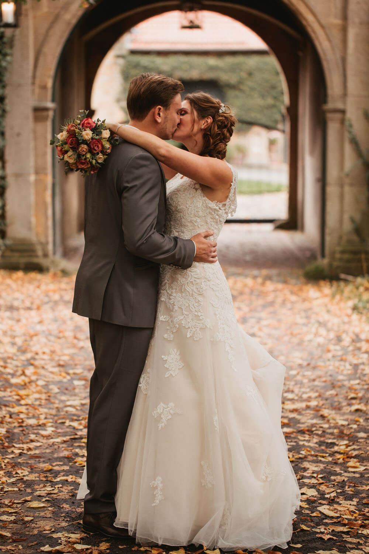 Brautpaar beim Fotoshooting kuesst sich