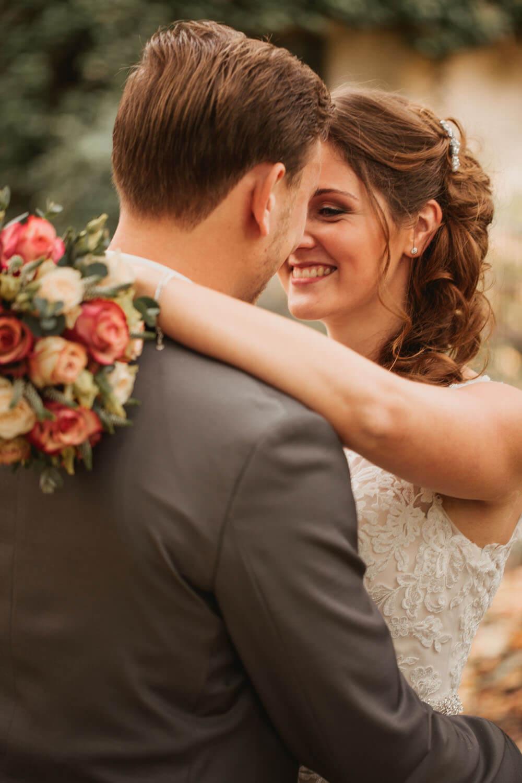 Braut umarmt den Braeutigam beim Fotoshooting. Hochzeitsfotos in Belm.
