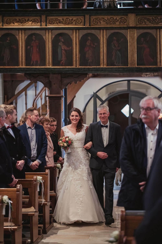 Vater zieht mit Braut in die Kirche. Hochzeitsfotos in Belm.