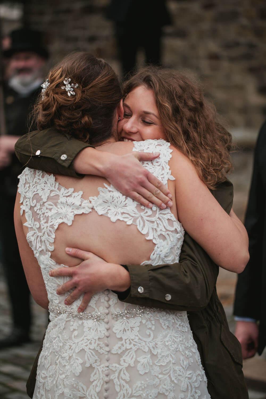Gute Freundin umarmt die Braut bei der Gratulation. Hochzeitsfotos in Belm.