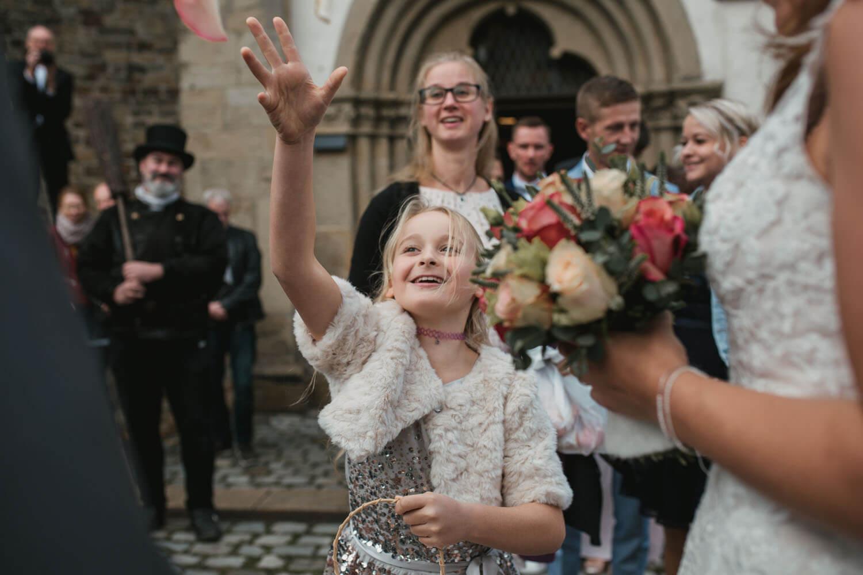 Blumenkind wirft Blumen vor der Kirche. Im Vordergrund das Hochzeitspaar. Hochzeitsfotos in Belm.