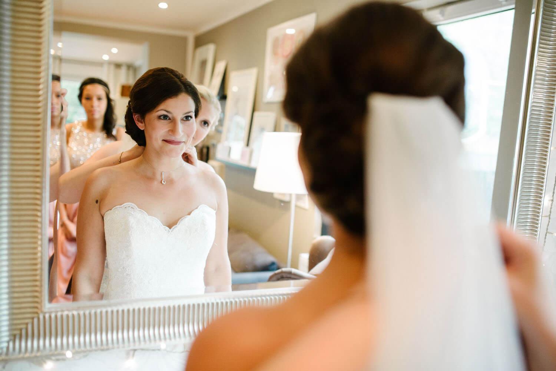 Braut steht beim Getting Ready vor dem Spiegel. Dahinter die Brautjunger. Kirchliche Trauung Osnabrück.