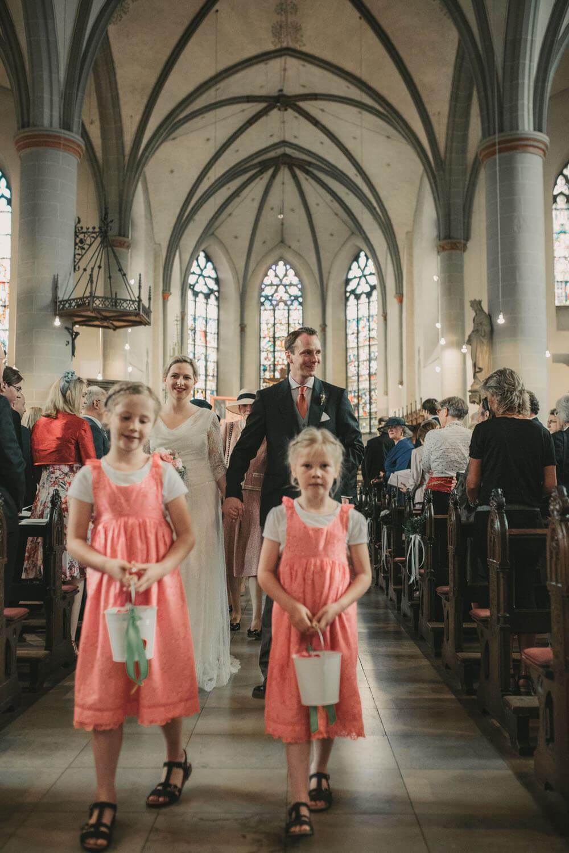 Auszug des Brautpaares mit Blumenmädchen im Vordergrund. Hochzeitsfotograf - Reportage Carl und Louise
