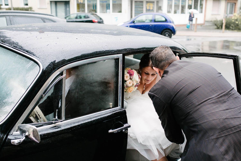 Brautvater hilft der Braut aus dem Auto. Kirchliche Trauung Osnabrück.