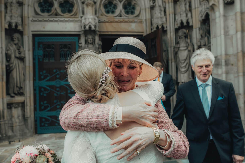 Brautmutter gratuliert der Braut vor der Kirche.