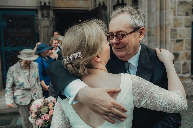 Brautvater gratuliert der Braut vor der Kirche.