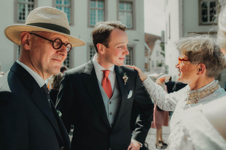 Gäste Gratulieren dem Bräutigam vor der Kirche. Hochzeitsfotograf - Reportage Carl und Louise
