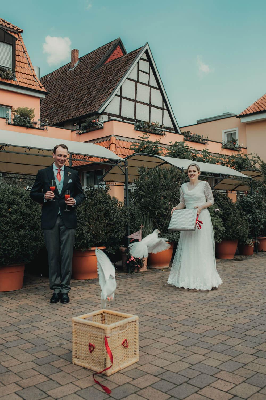 Brautpaar lässt weiße Tauben steigen. Hochzeitsfotograf - Reportage Carl und Louise