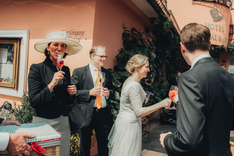 Gäste trinken beim Sektempfang und stoßen mit dem Brautpaar an. Hochzeitsfotograf - Reportage Carl und Louise