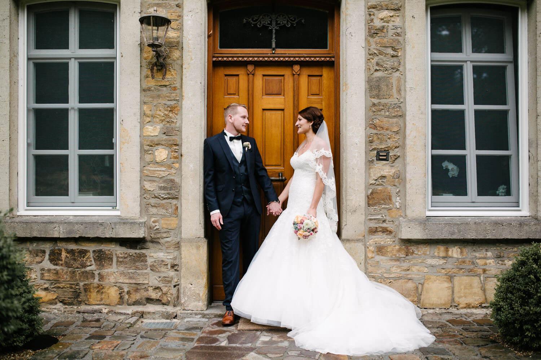 Hochzeitspaar lehnt an einer Tür und hält die Hände. Kirchliche Trauung Osnabrück.