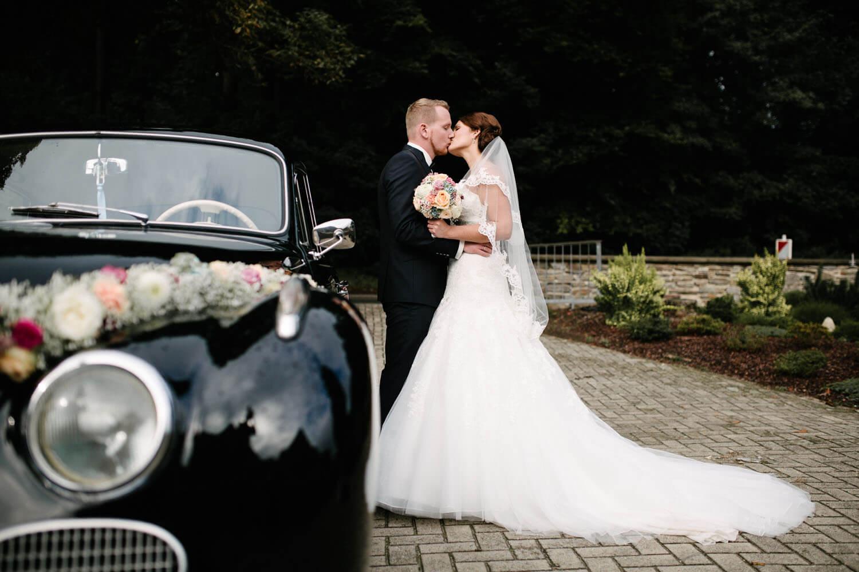 Küssendes Brautpaar vor dem Hochzeitswagen. Kirchliche Trauung Osnabrück.
