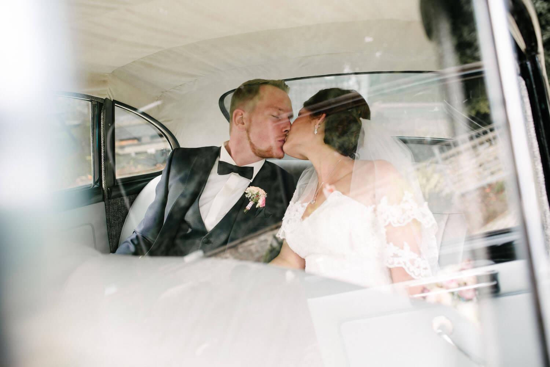 Brautpaar küsst sich im Auto. Kirchliche Trauung Osnabrück.