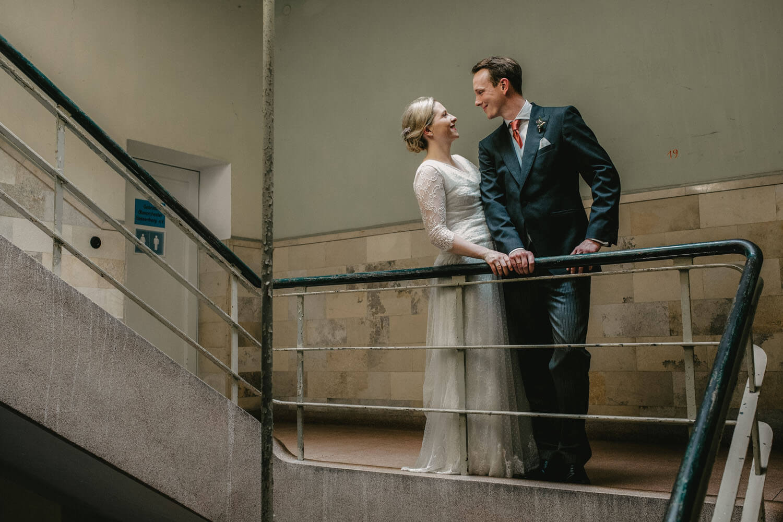 Brautpaar lehnt lässig am Geländer. Hochzeitsfotograf - Reportage Carl und Louise