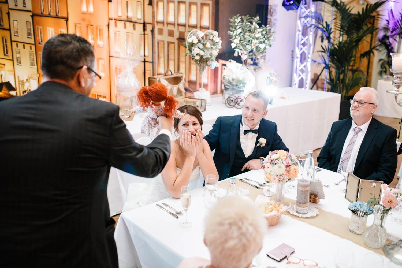 Brautvater zeigt der Braut ihre erste Puppe während der Hochzeitsfeier. Kirchliche Trauung Osnabrück.