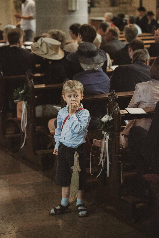 Kleiner Junge wartet aufgeregt auf das Brautpaar in der Kirche.