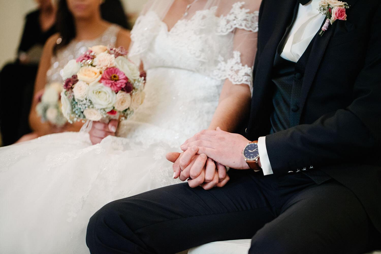 Brautpaar hält während der Trauung die Hände. Kirchliche Trauung Osnabrück.