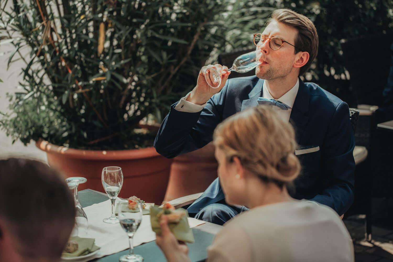 Gast beim Sektempfang trinkt Sekt am Tisch.