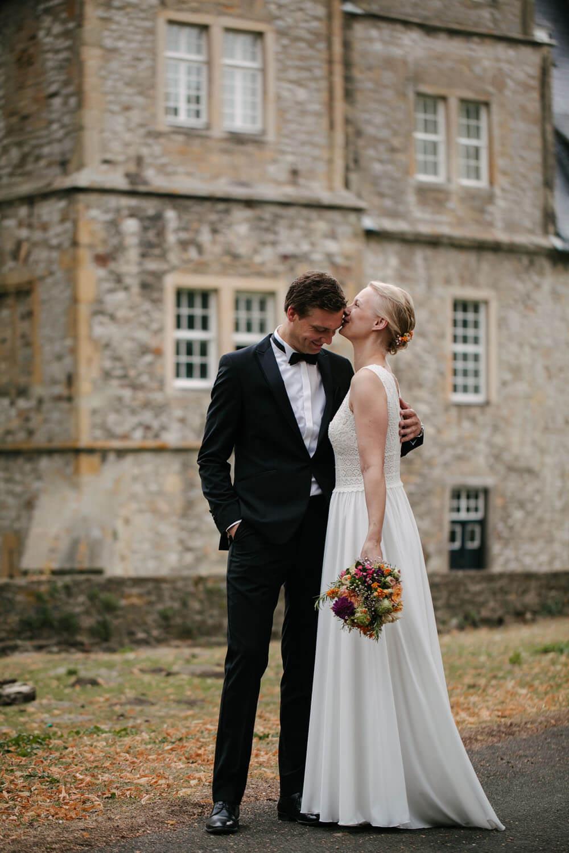 Fotoshooting Hochzeitspaar. Die Braut kuesst den Braeutigam auf die Stirn