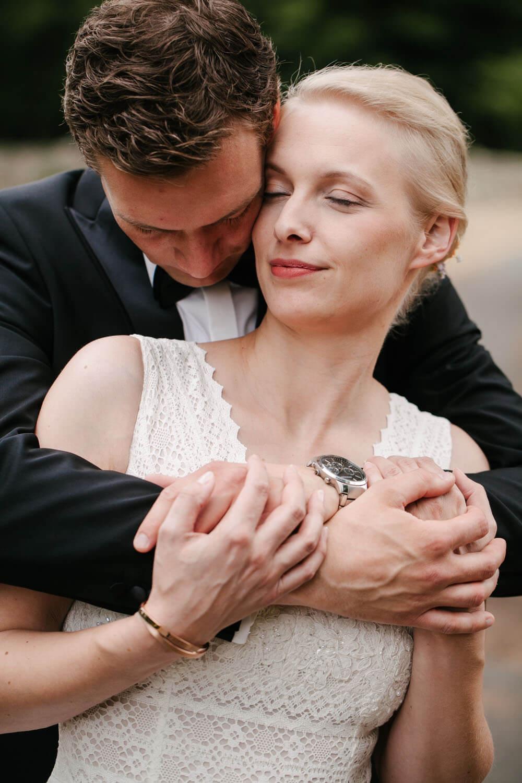 Braeutigam umarmt Braut mit geschlossenen Augen von hinten.