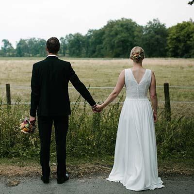 Brautpaar haelt sich an der Hand und schaut auf ein Feld hinaus.