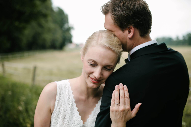Braut lehnt sich mit geschlossenen Augen an die Schulter des Bräutigams. Er versteckt sein Gesicht hinter ihrem Kopf.