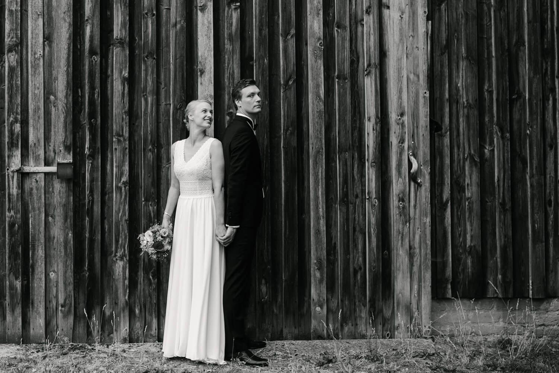 Brautpaar steht Ruecken an Ruecken vor einer Holzwand. Sie schaut zu ihm. Hochzeit in Melle