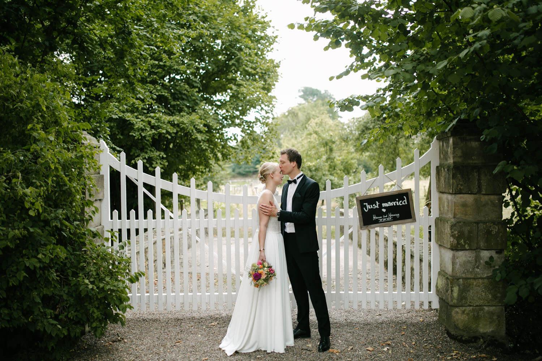 Brautpaar vor weißem Tor. Er küsst sie auf die Stirn. Schild mit Just married haengt am Zaun. Hochzeit in Melle