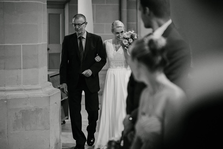Brautvater führt Braut zum Altar. Sie weint und schaut den Braeutigam im Vordergrund an. Hochzeit in Melle