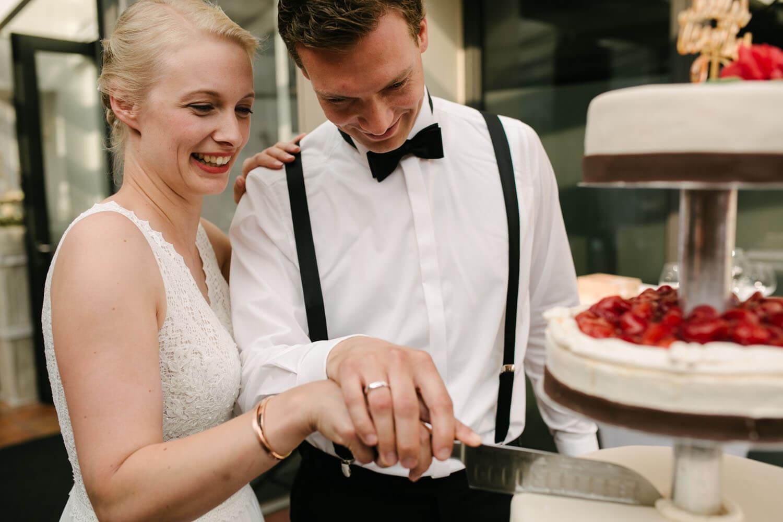 Brautpaar schneidet die Hochzeitstorte mit Erdbeeren an. Hochzeit in Melle.