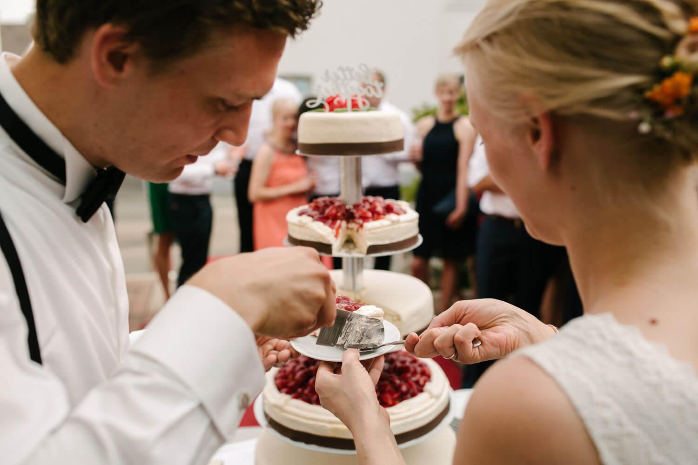 Braeutigam entnimmt das erste Stueck Hochzeitstorte Hochzeit in Melle.