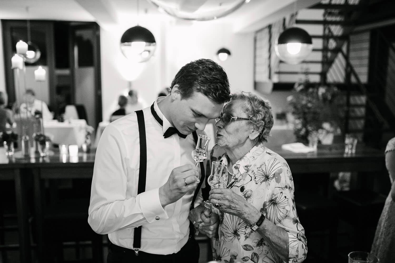 Großmutter fluestert Braeutigam etwas ins Ohr. Sie prosten sich zu. Hochzeit in Melle.