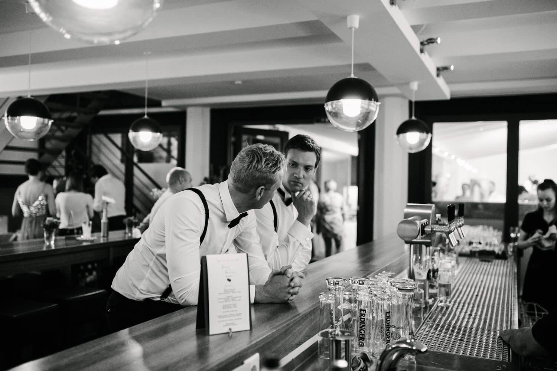 Braeutigam und Trauzeuge alleine an der Bar. Sie unterhalten sich. Hochzeit in Melle.