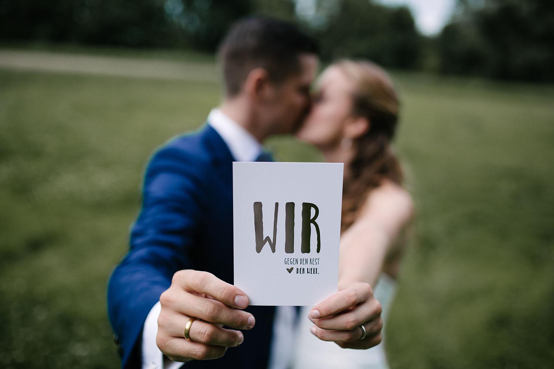 Brautpaar haelt beim Fotoshooting kuessend eine Karte in die Kamera. Hochzeitsreportage an der alten Wassermühle.