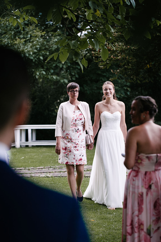 Laechelnde Braut wird von ihrer Mutter zur freien Trauung geleitet. Der Braeutigam wartet gespannt im Vordergrund. Hochzeitsreportage an der alten Wassermühle.