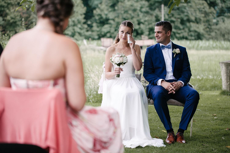 Weinende Braut bei der freien Trauung. Trauzeugin im Vordergrund. Hochzeitsreportage an der alten Wassermühle.