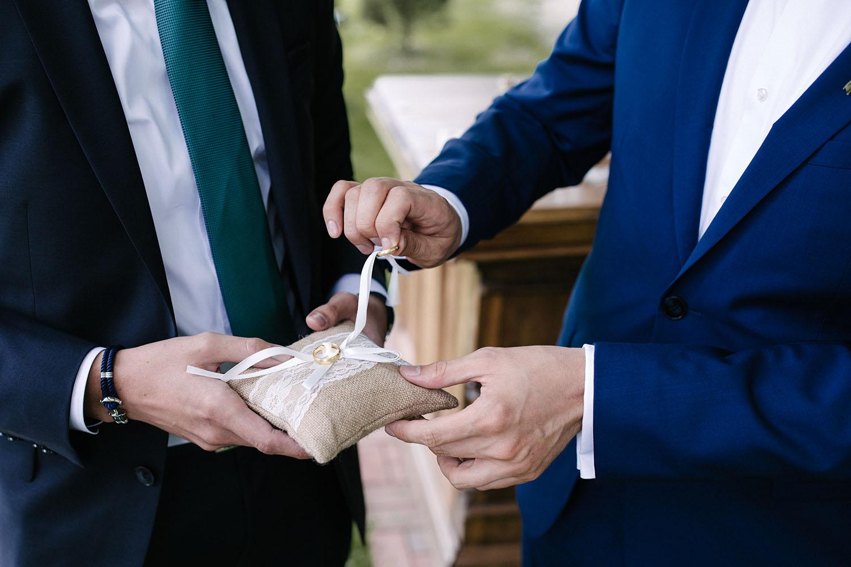 Nahaufnahme von dem Braeutigam, waehrend er den Ehering vom Kissen nimmt. Hochzeitsreportage an der alten Wassermühle.