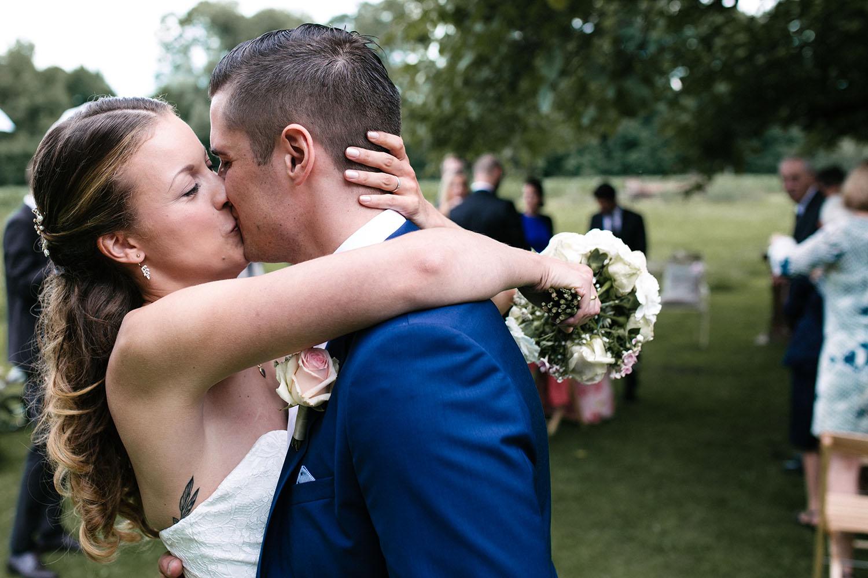 Nahaufnahme von leidenschaftlichen Kuss des Brautpaares. Hochzeitsreportage an der alten Wassermühle