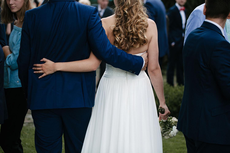 Ruecken des umarmenden Brautpaares. Hochzeitsreportage an der alten Wassermühle
