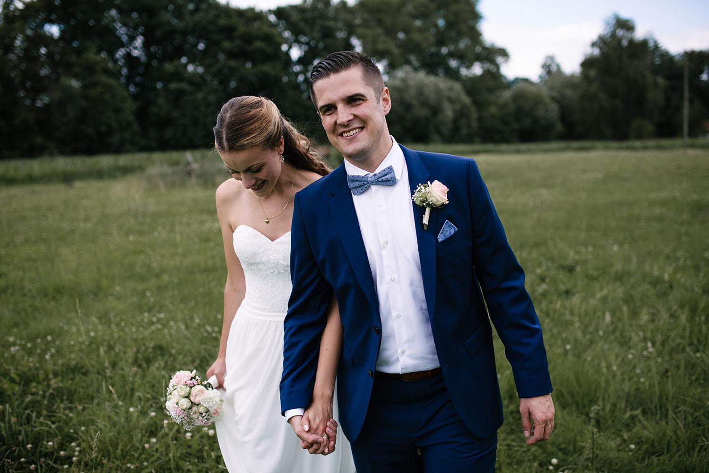 Brautpaar spaziert während des Fotoshootings ueber ein Feld. Hochzeitsreportage an der alten Wassermühle