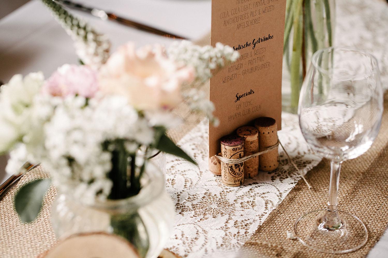 Getraenkekarte steckt in einer Halterung aus Weinkorken. Blumen im Vordergrund. Hochzeitsreportage an der alten Wassermühle