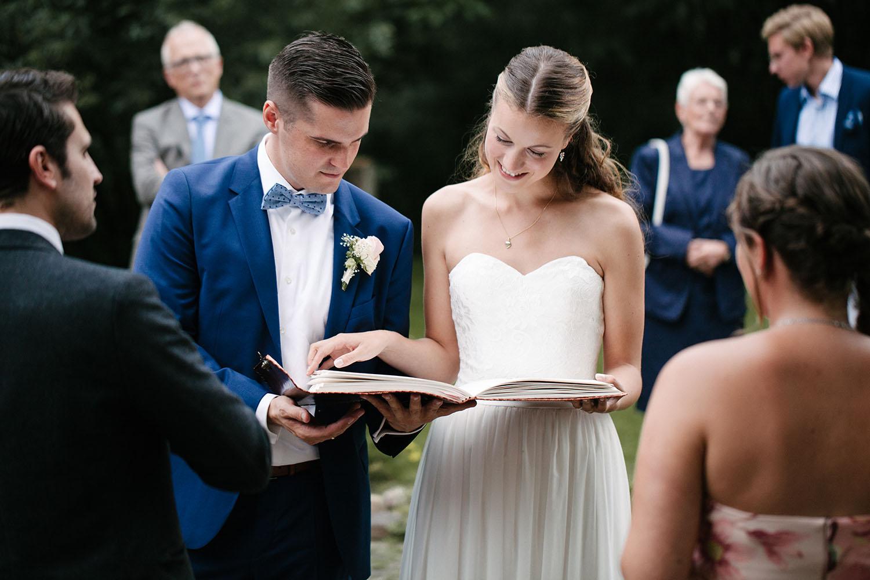 Brautpaar schaut in sich ein geschenktes Fotobuch der Trauzeugen an.