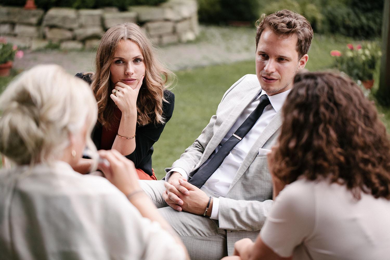 Gaeste auf der Hochzeit unterhalten sich.