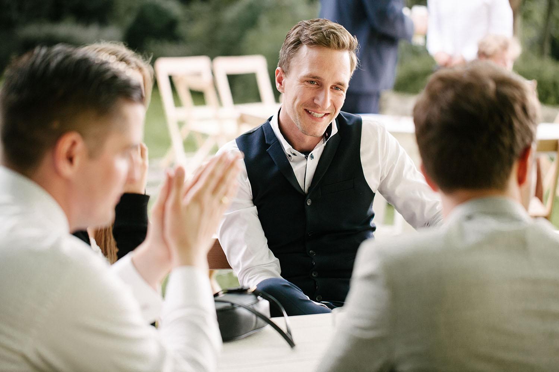 Lachende Gaeste auf der Hochzeit.