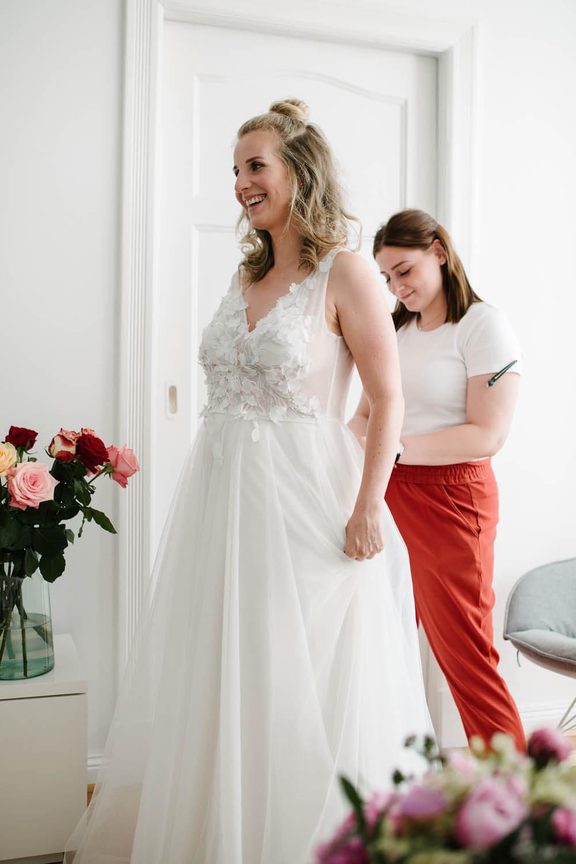 Visagistin bindet der lachenden Braut das Hochzeitskleid zu. im Vordergrund steht der Brautstrauss.